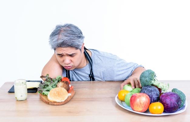 مردی که بعد از عمل اسلیو معده دو وعده غذایی میوه و سبزیجات دارد و بین آن ها غذاهای سالمی که به کاهش وزن بعد از عمل اسلیو کمک می کند را انتخاب می کند